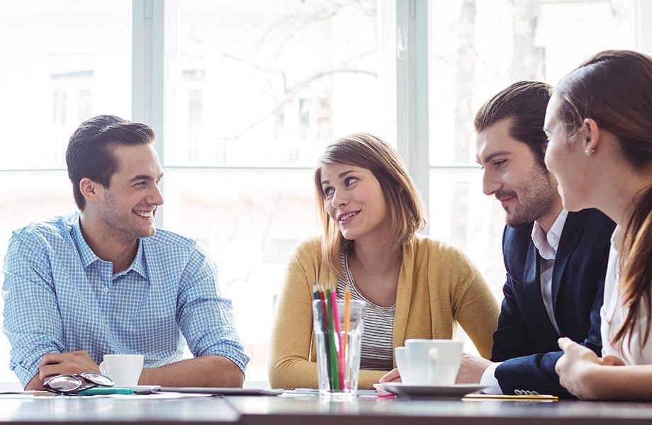 4 personer til møde ved et bord.